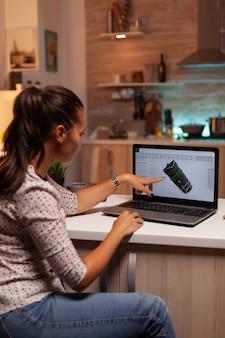 Engenheiro apontando para o projeto de turbina no laptop enquanto trabalhava no laptop durante a noite industrial ...