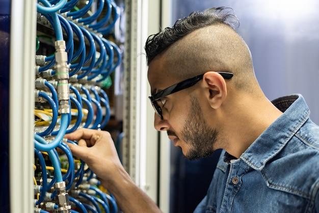 Engenheiro árabe ocupado conectando cabos de banda larga
