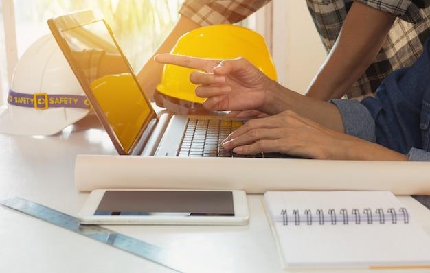 Engenheiro arquiteto usando laptop para trabalhar com capacete amarelo e laptop na mesa.