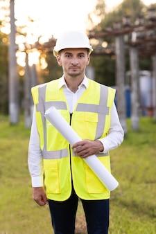 Engenheiro arquitetônico investidor bem-sucedido usando capacete e colete de segurança
