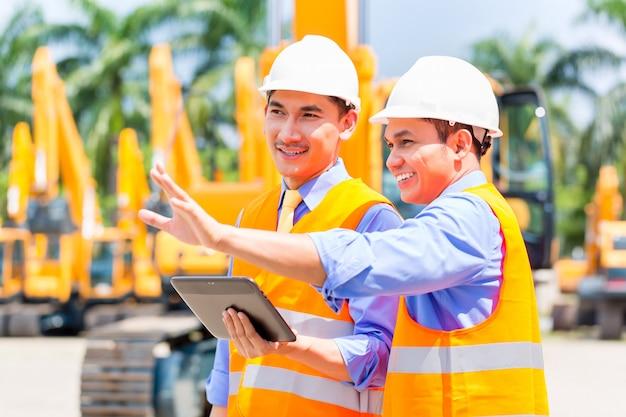 Engenheiro asiático, discutindo planos no canteiro de obras