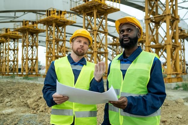 Engenheiro barbudo com planta mostrando a nova construção para um colega africano