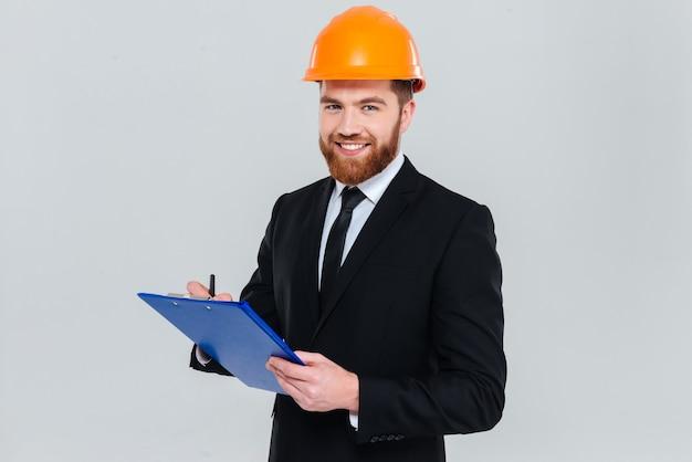 Engenheiro barbudo sorridente de terno e capacete segurando uma prancheta