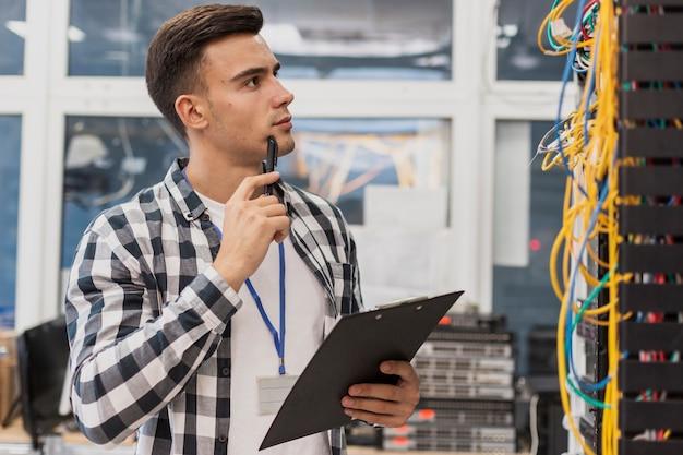 Engenheiro bonito com prancheta na sala do servidor