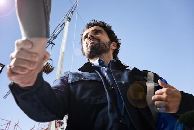 Engenheiro bonito dando um aperto de mão em um canteiro de obras