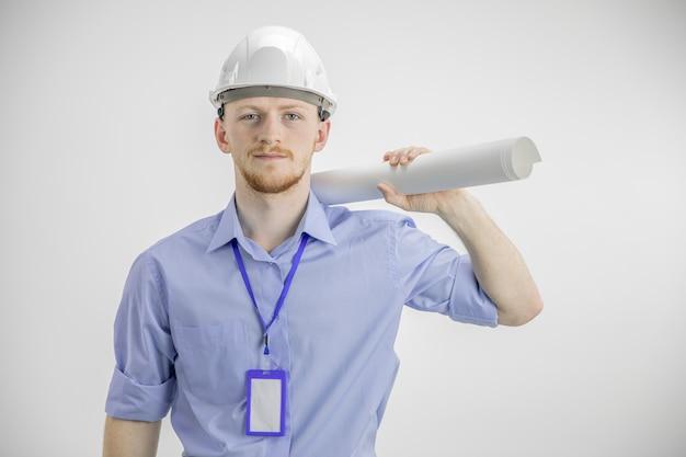 Engenheiro bonito no capacete segurando blueprint roll no ombro homem de sucesso