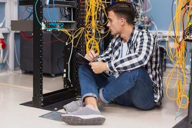 Engenheiro bonito trabalhando na sala do servidor