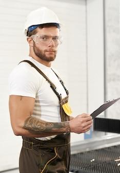 Engenheiro brutal em uniforme segurando a pasta, posando na fábrica