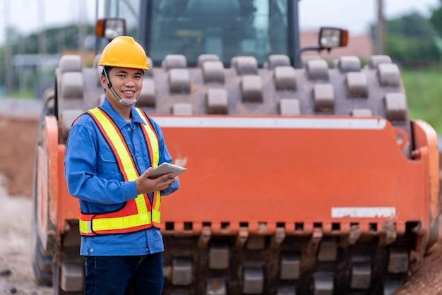 Engenheiro civil asiático usa um capacete no canteiro de obras de estradas.