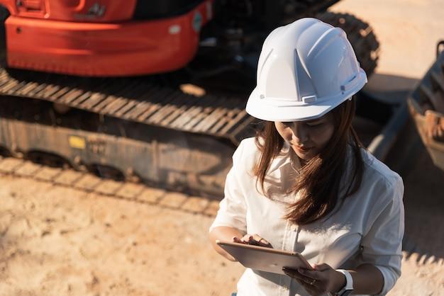 Engenheiro civil da mulher asiática com o canteiro de obras branco da visita do capacete de segurança.