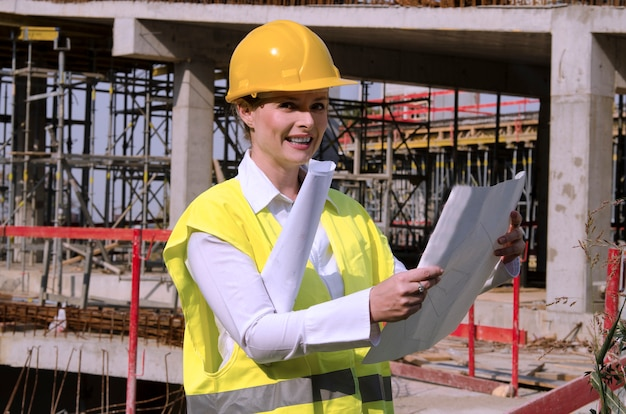 Engenheiro civil de mulher no canteiro de obras, controlando planos de arquitetura