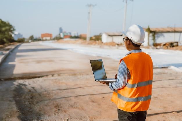 Engenheiro civil no canteiro de obras usando o computador laptop, verificando o trabalho. gestão no canteiro de obras.