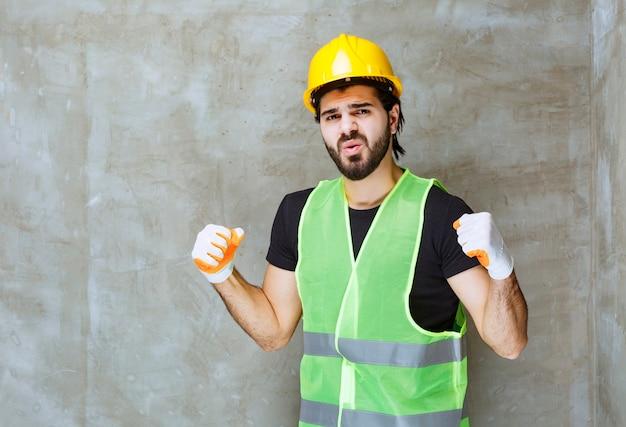 Engenheiro com capacete amarelo e luvas industriais mostrando sinal de satisfação