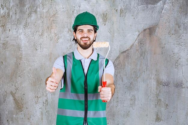 Engenheiro com equipamento amarelo e capacete segurando um rolo de acabamento e mostrando o polegar para cima.
