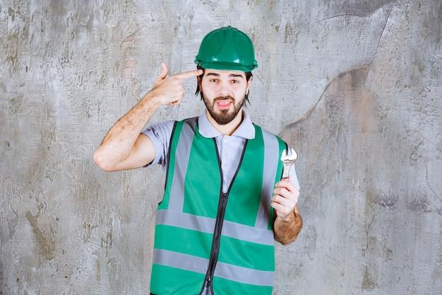 Engenheiro com equipamento amarelo e capacete segurando uma chave metálica e parece confuso e pensativo.