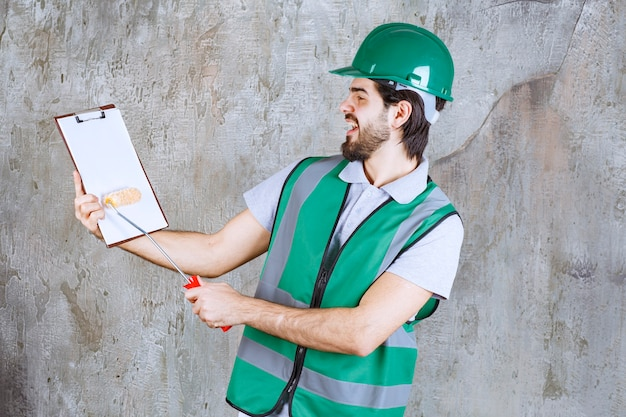 Engenheiro com roupa amarela e capacete segurando um rolo de acabamento e uma folha de papel e lendo.