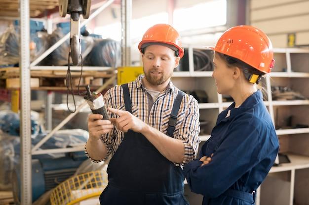 Engenheiro confiante mostrando parte do novo equipamento para seu colega ou trainee enquanto descreve sua finalidade