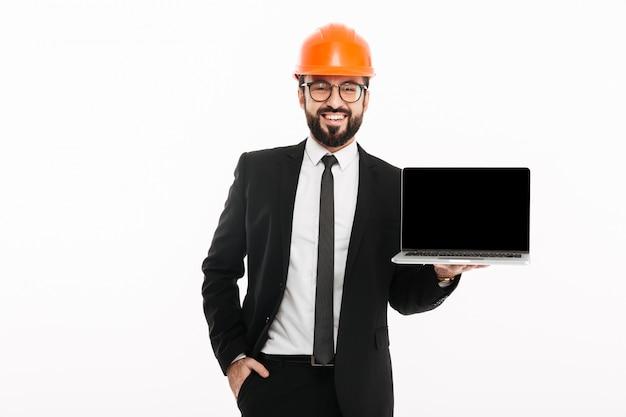 Engenheiro construtor alegre usando capacete mostrando a exibição do laptop