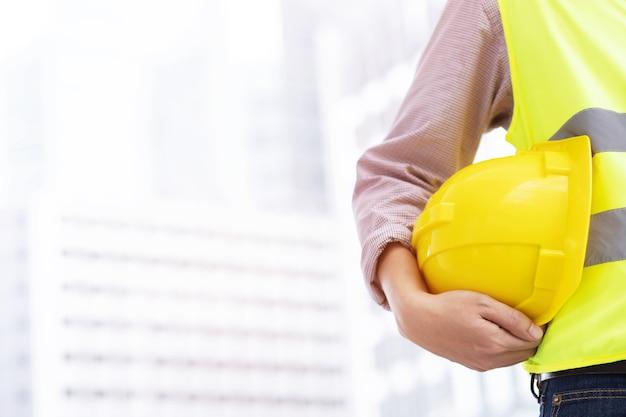 Engenheiro construtor de topografia com equipamento de trânsito de teodolito no local de construção ao ar livre durante o trabalho de levantamento