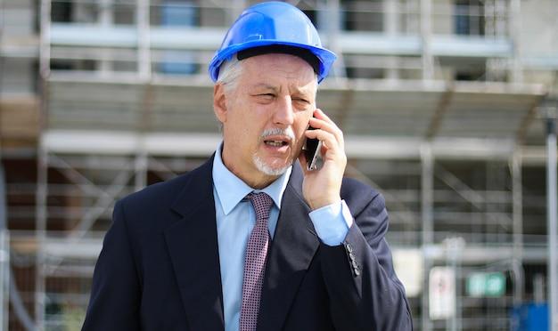Engenheiro construtor no canteiro de obras falando ao telefone