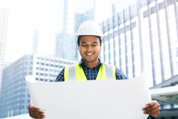 Engenheiro construtor topógrafo com equipamento de trânsito de teodolito no local de construção