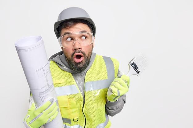 Engenheiro da indústria profissional surpreso posa com projeto arquitetônico segurando pincel redecorando a casa de acordo com o projeto de arquibancadas