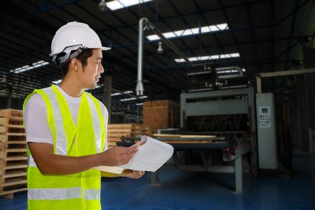 Engenheiro da indústria verifique a fábrica de madeira e as máquinas de produção.