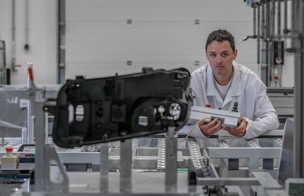 Engenheiro da qualidade realiza medições 3d de peças fundidas de plástico com a ajuda de um robô para a indústria automotiva