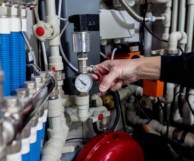 Engenheiro de aquecimento que fixa o sistema de aquecimento moderno na sala de caldeira. unidade de controle automático.