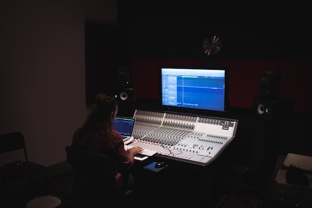 Engenheiro de áudio masculino usando mixer de som