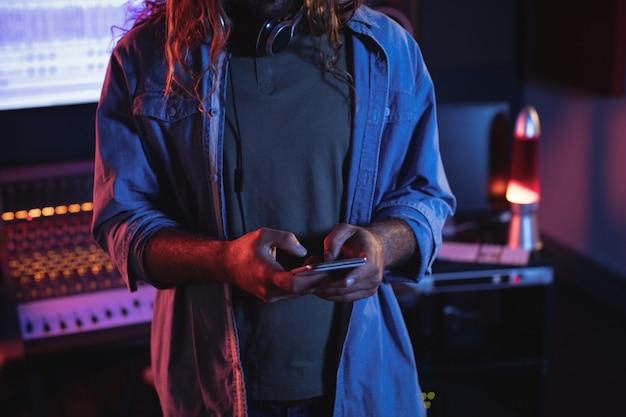 Engenheiro de áudio masculino usando telefone celular