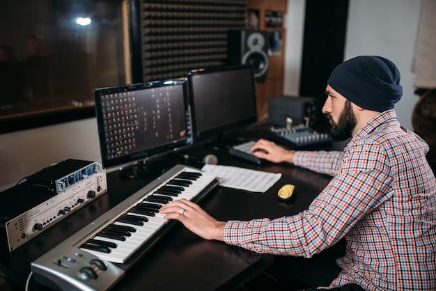 Engenheiro de áudio trabalha com teclado musical em estúdio. tecnologia profissional de gravação de som digital