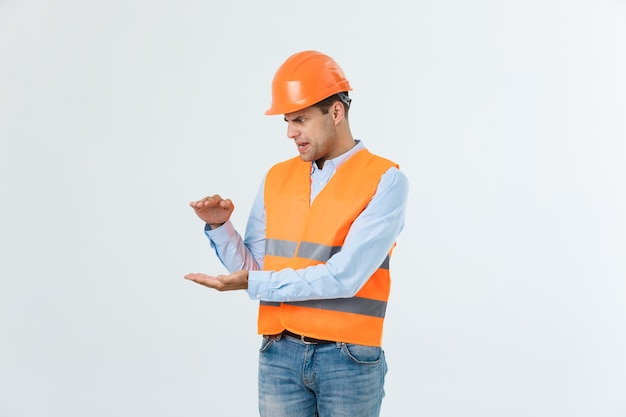 Engenheiro de barba feliz segurando a mão ao lado e explicando algo, cara vestindo camisa caro e jeans com colete amarelo e capacete laranja, isolado no fundo branco.