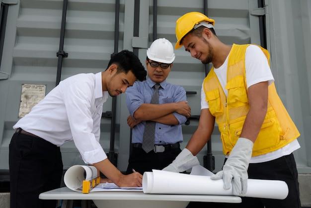 Engenheiro de campo escrever plano de construção em papel para relatar gerente de engenharia sênior