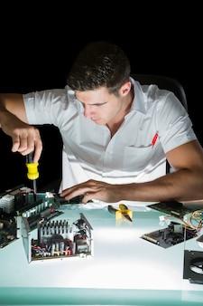 Engenheiro de computação bonito trabalhando de noite com chave de fenda