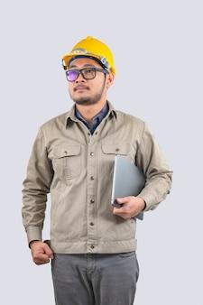 Engenheiro de computação jovem homem asiático com laptop e capacete amarelo