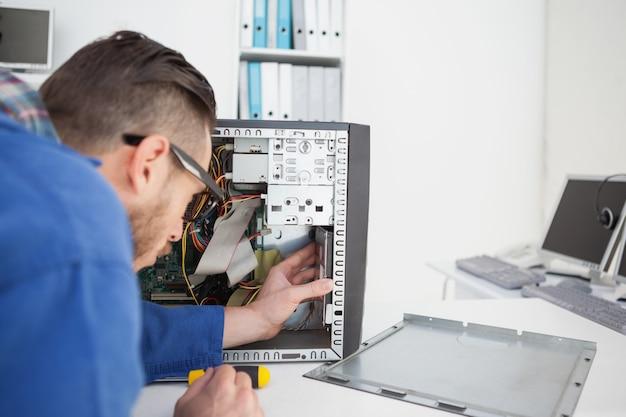 Engenheiro de computação trabalhando no console quebrado com chave de fenda
