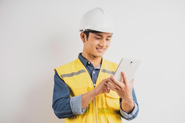 Engenheiro de construção asiático lendo o desenho técnico