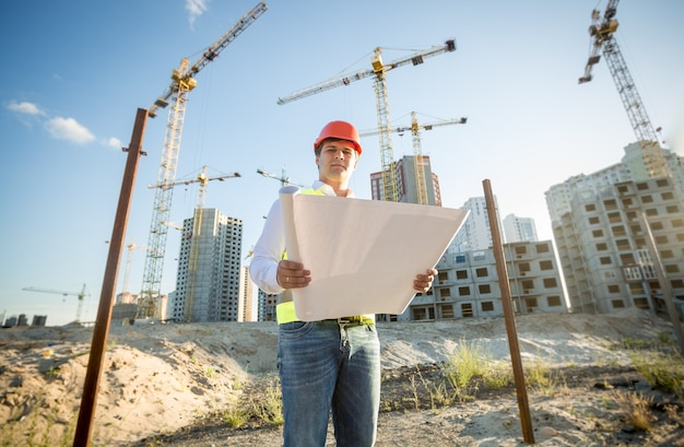 Engenheiro de construção com capacete de segurança inspecionando plantas no canteiro de obras
