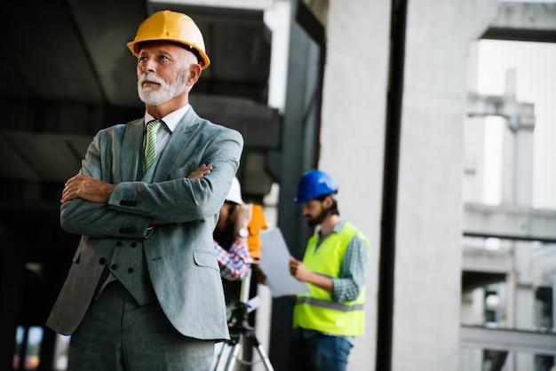 Engenheiro de construção confiante, arquiteto, empresário com capacete de segurança trabalhando no canteiro de obras