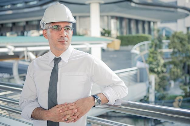 Engenheiro de construção confiante no capacete, olhando para projetos de construção.