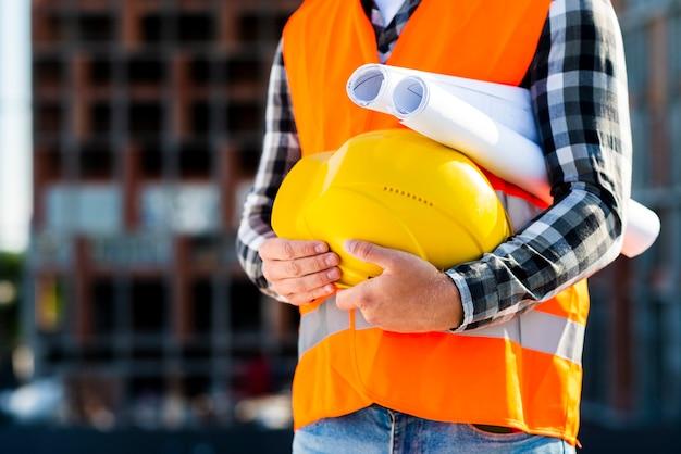 Engenheiro de construção de close-up segurando o capacete