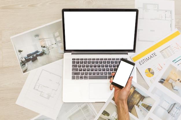 Engenheiro de construção e mesa do arquiteto com projetos de casa, laptop, ferramentas