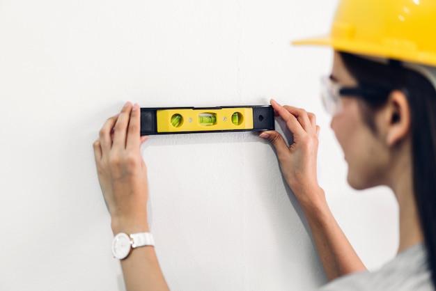 Engenheiro de construção jovem em um capacete amarelo trabalhando e fazendo medições na parede na construção de site em casa