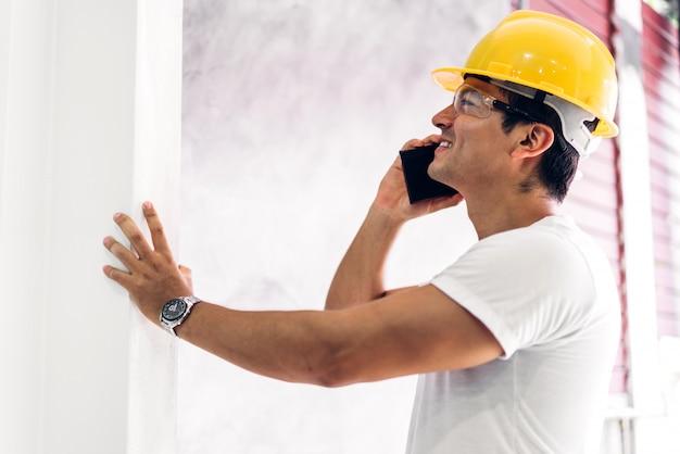 Engenheiro de construção jovem em um capacete amarelo trabalhando e procurando emprego para o projeto de planejamento na construção de site em casa