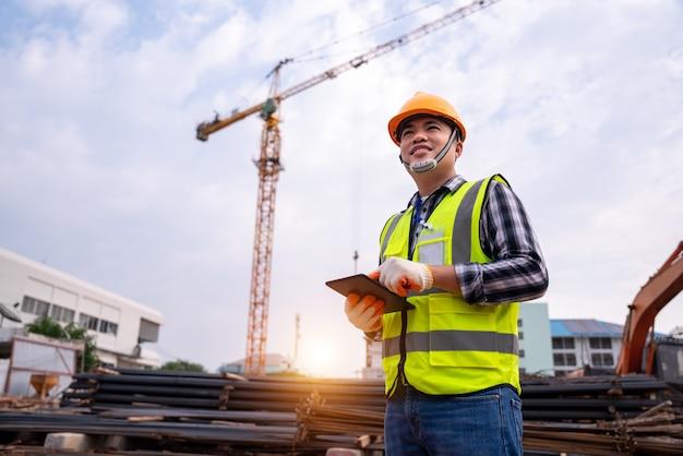 Engenheiro de construção masculino. arquiteto com um computador tablet em uma construção. jovem asiático olhando, construindo local de canteiro. conceito de construção ou engenheiro de construção