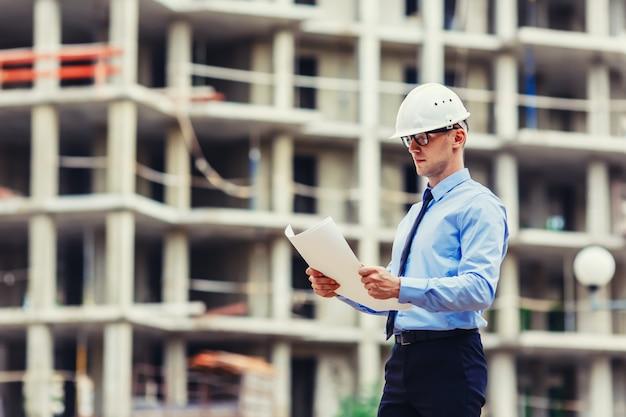 Engenheiro de construção no canteiro de obras, olhando para o desenho
