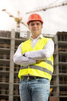 Engenheiro de construção sorridente com capacete de segurança olhando para a câmera