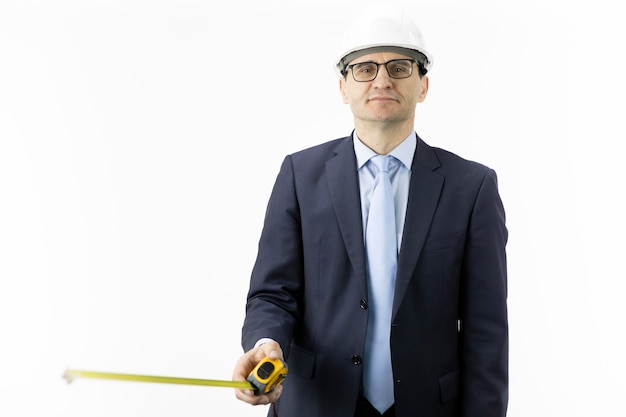 Engenheiro de construção sorridente no capacete com fita métrica nas mãos