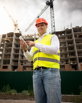 Engenheiro de construção sorridente posando com tablet digital